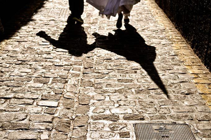 La sombra de un nazareno corriendo en los adoquines de Granada © Bisual Studio