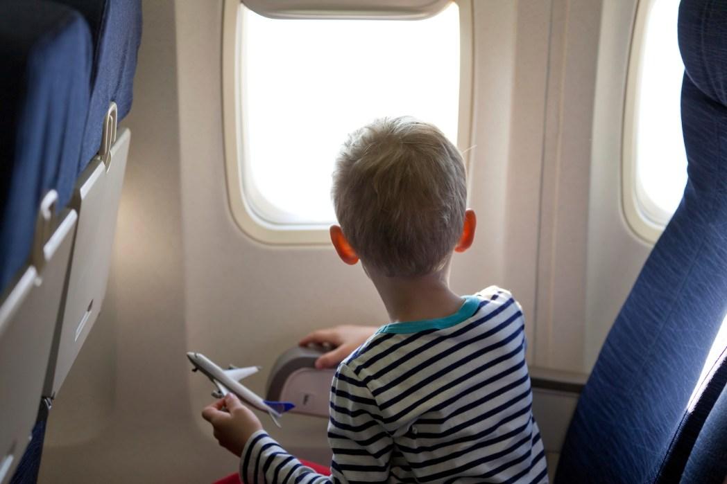 niño con avión de madera