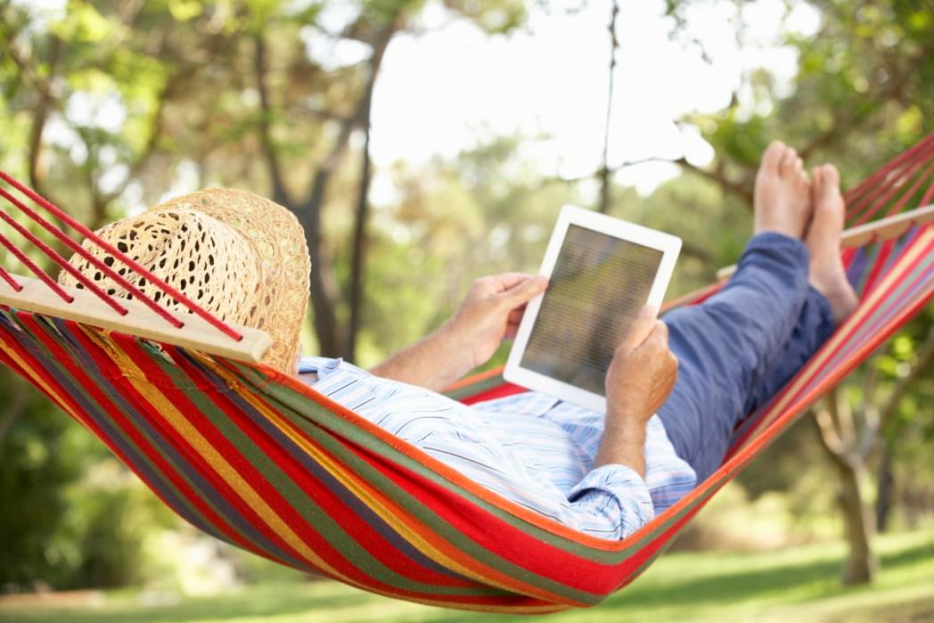 hombre leyendo un e-book en una hamaca
