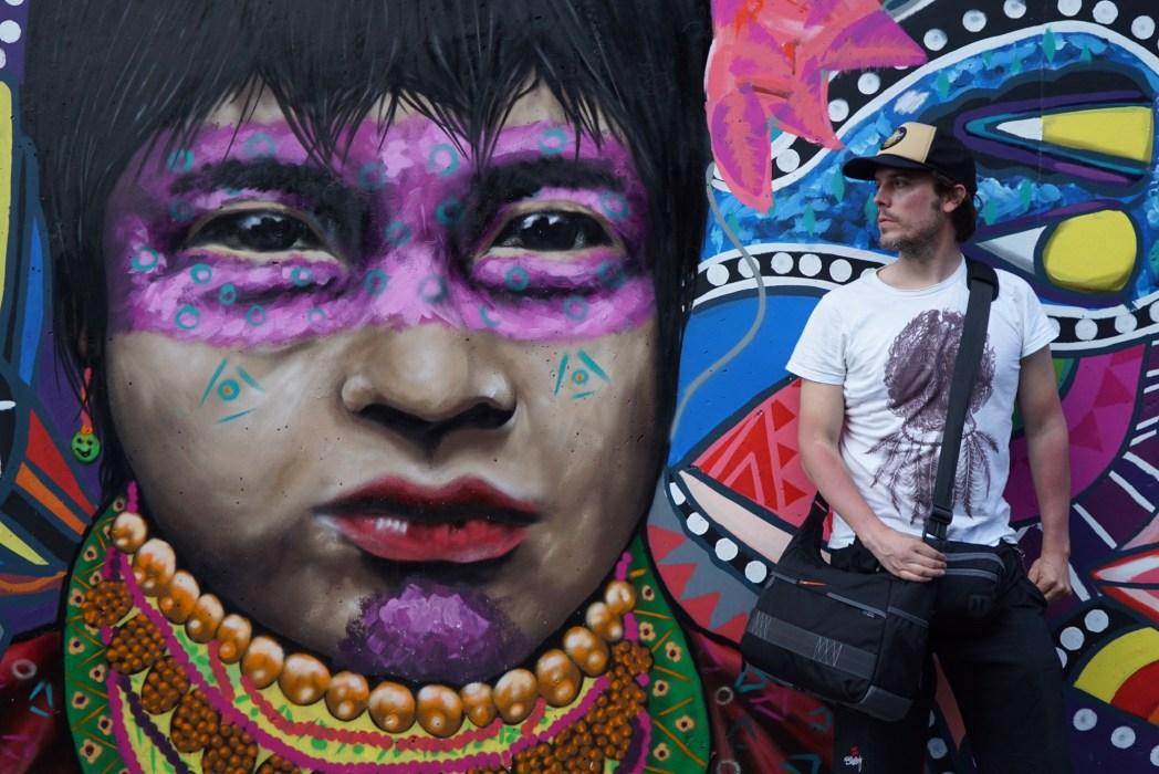 iosu lópez de mochileros tv delante de un grafitti en medellín colombia